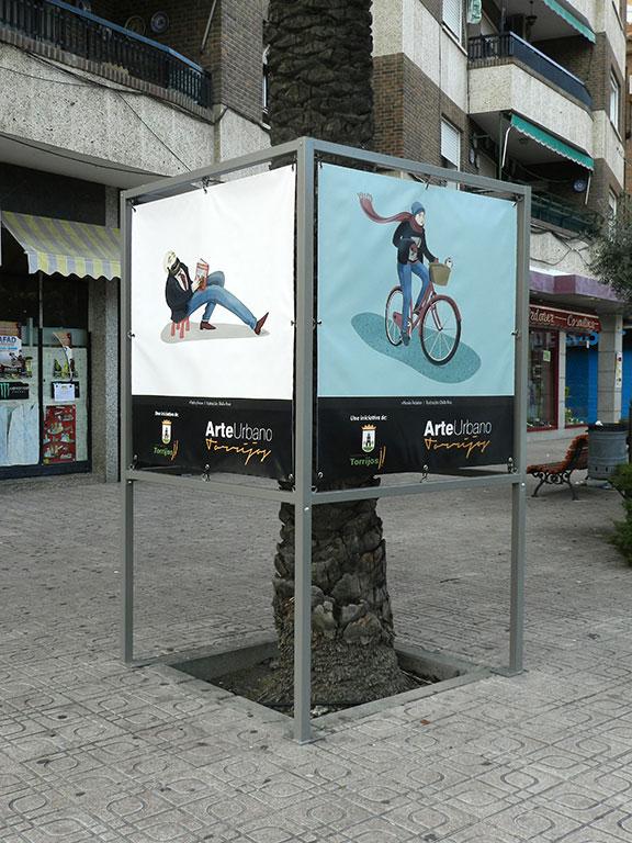 Exposición Arte Urbano en Torrijos, cubo con ilustraciones de lector y ciclista urbano