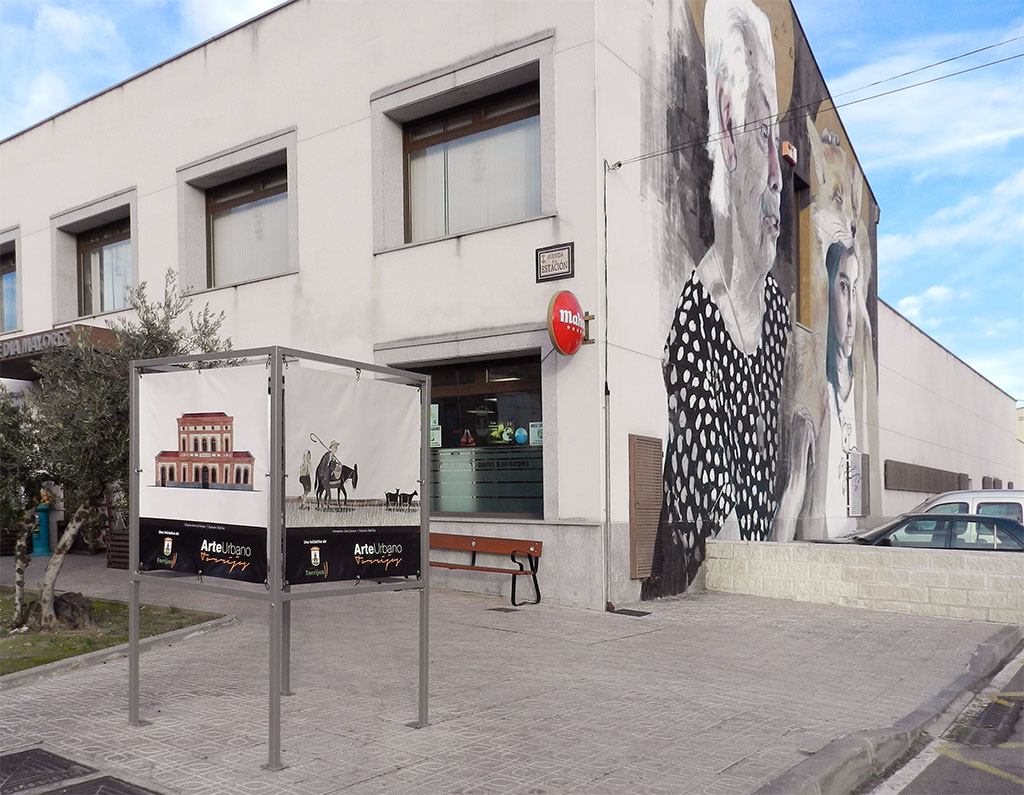 Exposición Arte Urbano en Torrijos, cubo con ilustraciones de la estación de tren y de Intemperie, con mural de Dan Ferrer de fondo